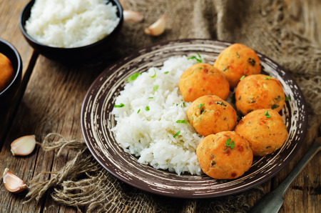 Salmon baked balls with rice on a wood background. toning. selective focus