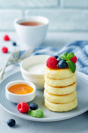 Cottage cheese pancakes with honey, sour cream and berries. toning. selective focus