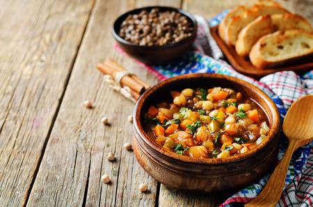 モロッコのスパイシーな緑のレンズ豆のひよこ豆のスープは、木製の背景に。調子。選択的フォーカス