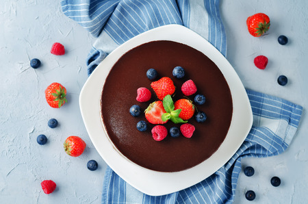 Triple chocolate mousse cake decorated with fresh berries. toning. selective focus 版權商用圖片