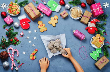 Christmas background with gifts, cookies, Christmas decoration and childrens hands holding cookies. toning. selective focus Stock Photo