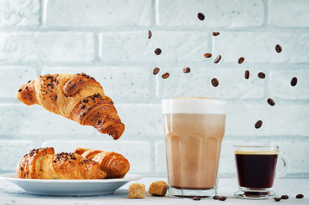 Different types of coffee with flying croissants. Espresso and mocha coffee. toning. selective focus