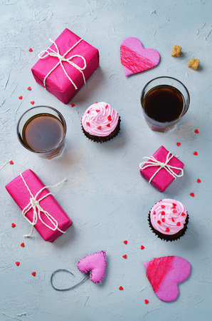 Stone background with gifts, cupcakes, coffee and card. toning. selective focus Imagens