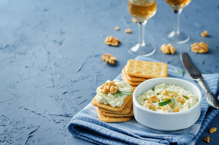 Blue cheese spread with walnuts on a stone background. toning. selective focus