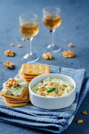 Blue cheese spread with walnuts on a stone background.
