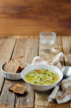 Zucchini Chicken Soup with bread on a wood background. toning. selective focus