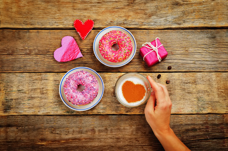 Wood background with cup of coffee, donuts, gift, hearts and womans hand. toning. selective focus