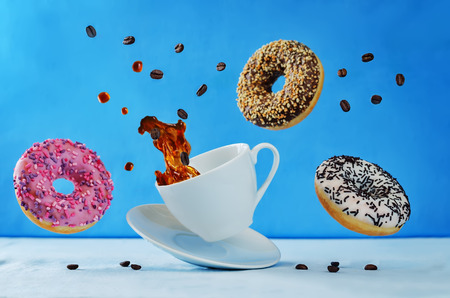 Flying multicolored donuts and a cup of coffee on a blue background. toning. selective focus