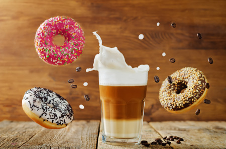 Flying multicolored donuts with a glass of coffee on a wood background. toning. selective focus Stock Photo