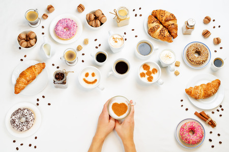 White background with woman's hand and different types of coffee and desserts to them. toning. selective focus Stockfoto