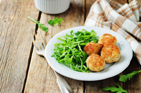 Turkey meatballs with arugula on a wood background. toning. selective focus