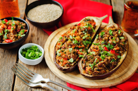 Minced meat quinoa vegetables stuffed eggplants on a wood background. toning. selective focus