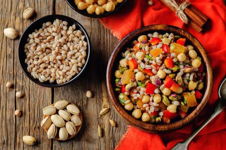 Insalata marocchina di pistacchi di orzo di ceci su uno sfondo di cemento. tonificante. messa a fuoco selettiva Archivio Fotografico - 94940743