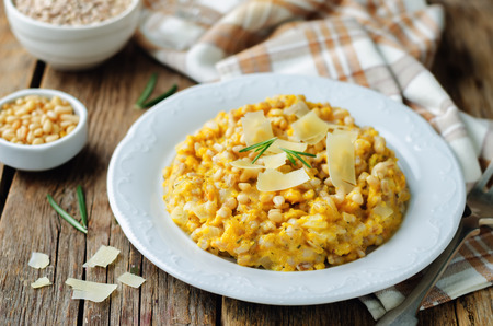 Roasted pumpkin and Pearl Barley Risotto on a wood background. toning. selective focus Archivio Fotografico
