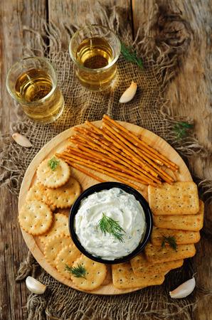 Feta cream cheese dill garlic dip with crackers. toning. selective focus