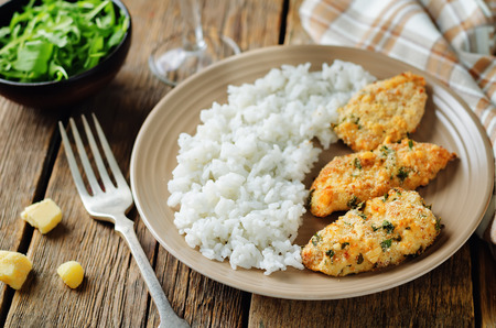 Baked Parmesan Parsley Crusted Chicken with rice on a wood background. toning. selective focus