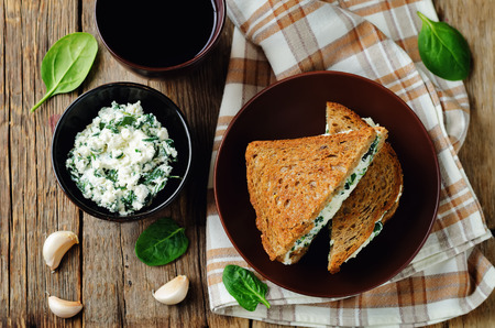 Ricotta spinach rye sandwich on a wood background. toning. selective focus
