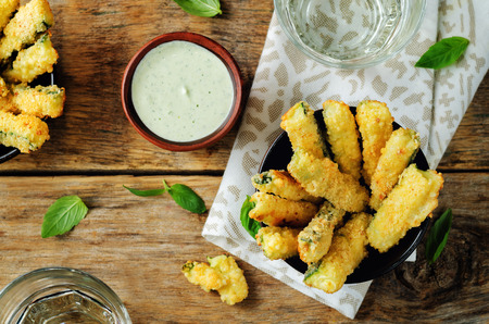 Baked Zucchini Fries with Pesto Greek yogurt sauce on a wood background. toning. selective focus