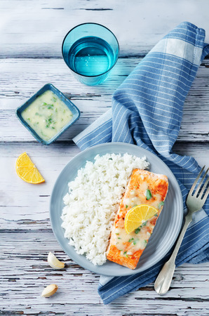 Salmon with Garlic Lemon Butter Sauce and rice on a wood background. toning. selective focus Stockfoto