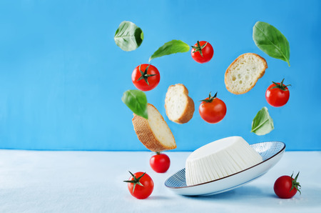 ricotta cheese with flying bread slices, tomatoes and Basil on a blue background with copy space. the toning. selective focus Stock Photo