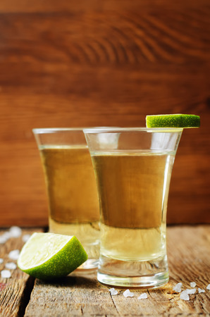 Tequila in glasses with lime and salt on a dark woody background. toning. selective focus 写真素材 - 95932056