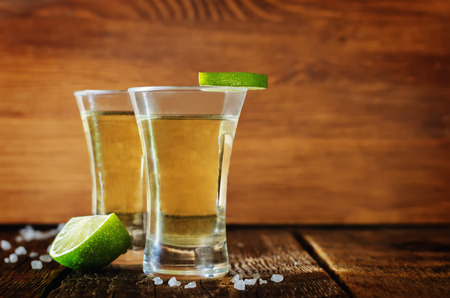 Tequila in glasses with lime and salt on a dark woody background. toning. selective focus Stock Photo