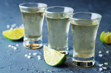 Tequila in glasses with lime and salt on a dark stone background. toning. selective focus 版權商用圖片