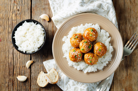 Baked Orange Chicken Meatballs with rice on a wood background. toning. selective focus Stock Photo