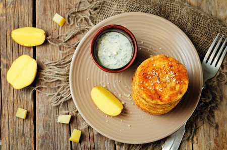 Mashed Potato Cheese Pancakes with Greek Yogurt Dill Sauce on a wood background. toning. selective focus