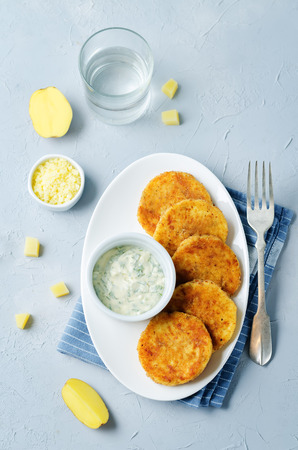 Mashed Potato Cheese Pancakes with Greek Yogurt Dill Sauce on a stone background. toning. selective focus