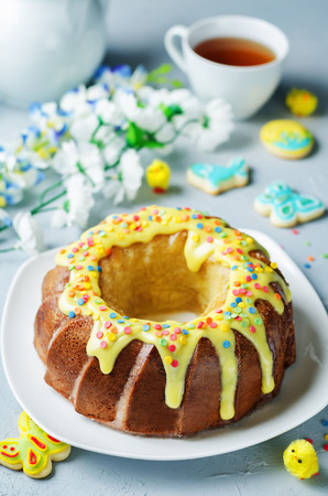 Easter Bundt cake with colorful topping and Easter Cookies on a stone background. tinting. selective focus Stock Photo