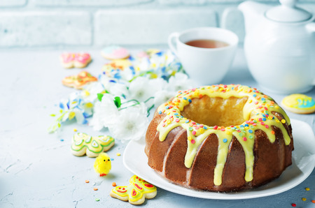 Easter Bundt cake with colorful topping and Easter Cookies on a stone background. tinting. selective focus Foto de archivo