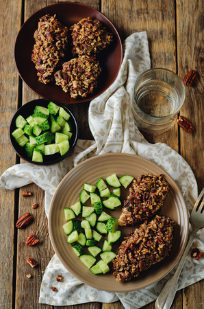 Pecan crust chicken breasts with cucumbers slices on a wood background. toning. selective focus