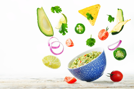 Guacamole with flying corn chips and ingredients to prepare it on a white background. toning. selective focus Stockfoto