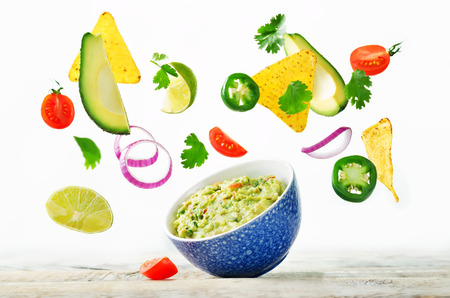 Guacamole with flying corn chips and ingredients to prepare it on a white background. toning. selective focus Stock Photo