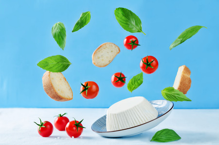 ricotta cheese with flying bread slices, tomatoes and Basil on a blue background. the toning. selective focus