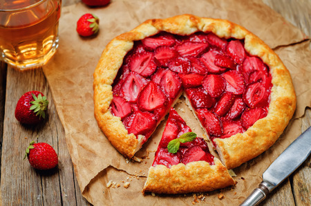 Strawberry galette with fresh strawberries on a wood background. toning. selective focus
