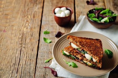 濃い木質の背景に新鮮な緑のモッツァレラグリルライ麦サンドイッチ。調子。選択的フォーカス 写真素材 - 99653635
