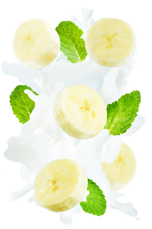 Flying banana slices with mint leaves and a spray of milk isolated. toning. selective focus Banco de Imagens - 103916594