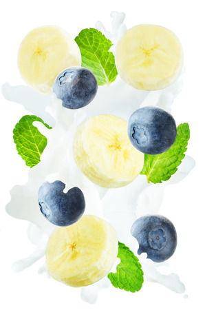 Flying blueberry and banana with mint leaves and a spray of milk isolated. toning. selective focus