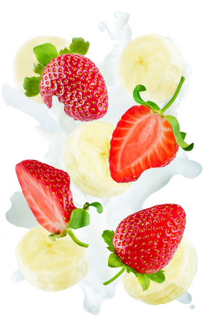 Flying strawberries and banana slices with a spray of milk isolated. toning. selective focus