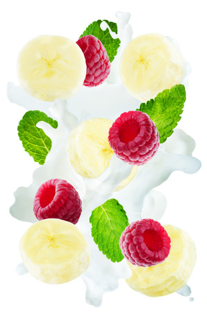 Flying raspberry and banana with mint leaves and a spray of milk isolated. toning. selective focus Banco de Imagens