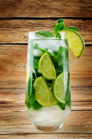 Mojito coctail  with fresh mint leaves and lime slice on a wood background. toning. selective focus