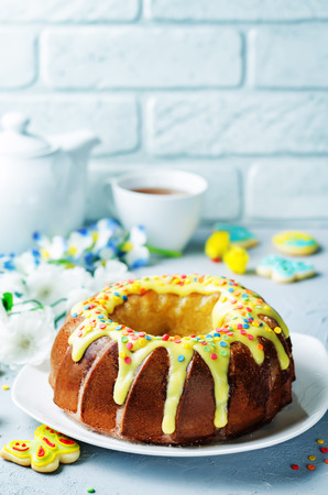 Easter Bundt cake with colorful topping and Easter Cookies on a stone background. tinting. selective focus