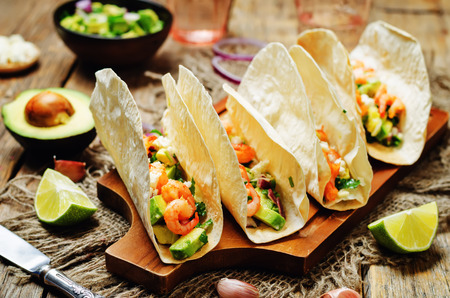 Shrimp tacos with avocado salsa on wood background. toning. selective focus