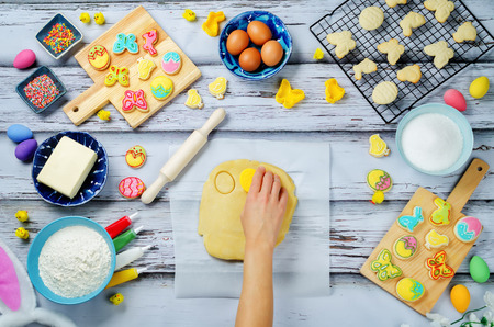 Womans hand with Sugar dough and ingredients for baking on a wood background. toning. selective focus Stock Photo