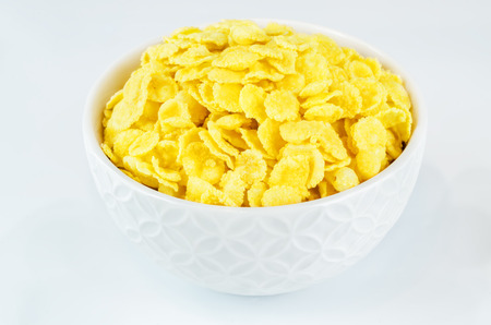 �¡orn flakes in a white bowl on a white background. toning. selective focus Banco de Imagens