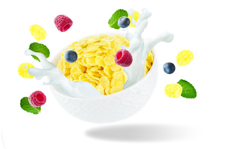 Healthy breakfast with milk, flying corn flakes, raspberries and blueberries isolated