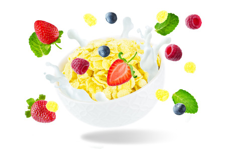 Healthy breakfast with milk, flying corn flakes, raspberries, strawberries and blueberries isolated Stock Photo
