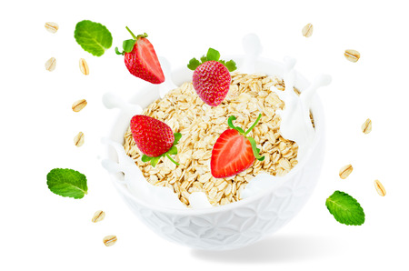 Oat bowl with splash of milk and flying strawberries isolated Stock Photo